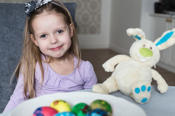 Smiling cute kid with easter eggs and plush bunny
