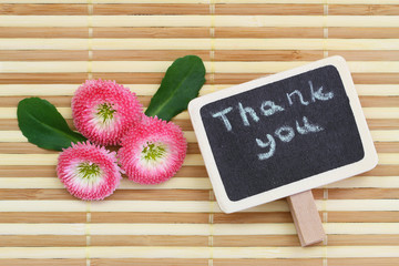 Thank you written on little blackboard with pink daisies