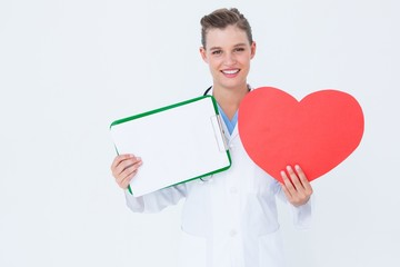 Happy doctor holding clipboard and heart card