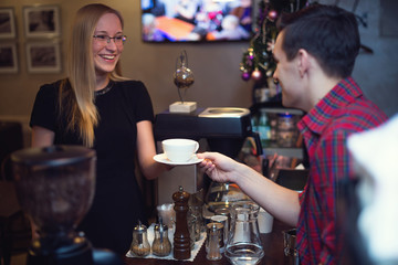Pretty blond girl taking her order with pleasant smile. Barista