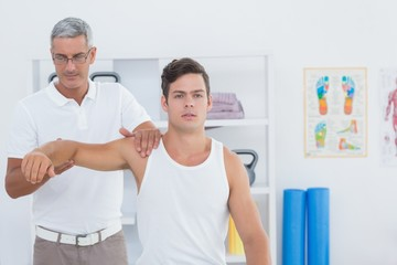 Doctor stretching a young man arm