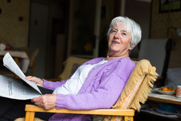 Senior woman reading morning newspaper