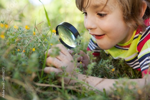 Happy little boy looking through magnifying glass - 80306273