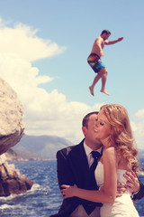 groom kissing bride on her neck near the sea