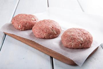 Fresh homemade raw  ground  beef burgers.
