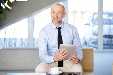 Portrait of a businessman with digital tablet at office
