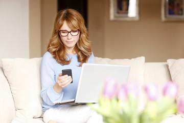 Portrait of business woman with laptop and mobile phone at home