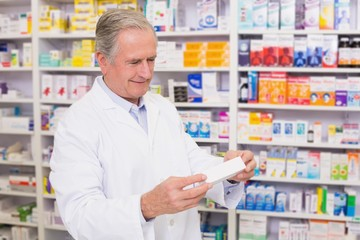 Pharmacist holding a box of pills while reading the label