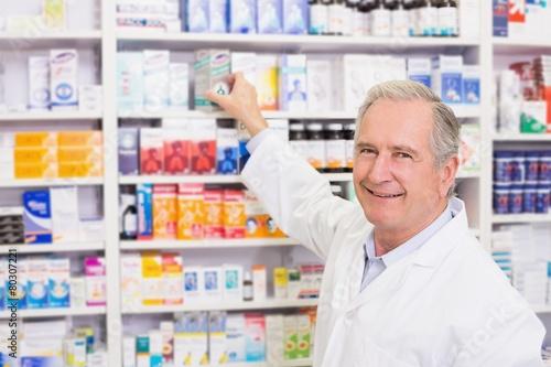 Papiers peints Pharmacie Smiling pharmacist taking medicine from shelf
