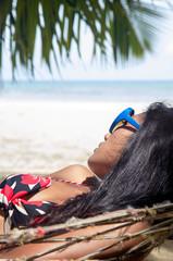 Woman is sleeping in the hammock on the tropical beach