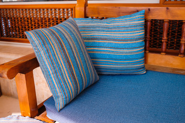 Two striped cushions lie on a wooden sofa