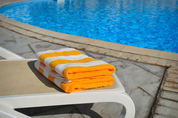 Two yellow striped towels lie on a sun-bed near a swimming pool