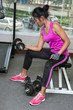 woman exercises with dumbbells in the gym