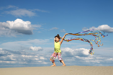 happy little girl playing on beach