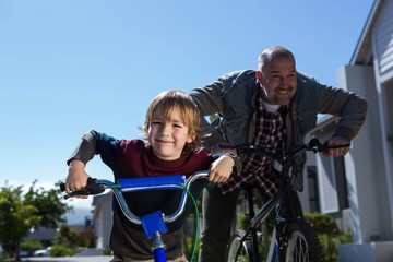 Happy father on a bike with his son