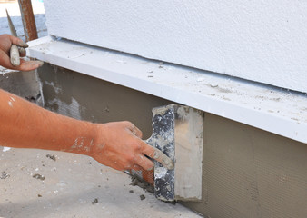 Man's hand plastering a wall insulation with trowel