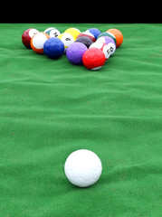 huge pool table with soccer balls instead of the billiard balls