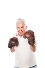 Senior man wearing boxing gloves smiling on white background