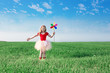 girl  holding a toy flower on background sky and field