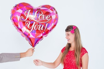 Geeky hipster offering red heart shape balloon to his girlfriend