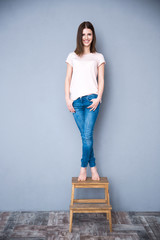 Smiling young woman standing on the chair