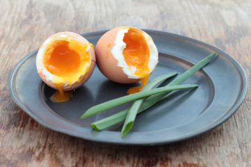 Two soft-boiled eggs on a tin plate.