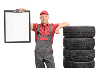 Mechanic holding a clipboard and leaning on tires