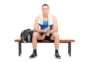 Athlete sitting on a bench holding a water bottle