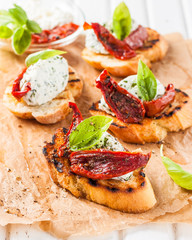 Italian bruschetta with cheese, basil and sun-dried tomatoes