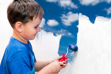 boy painting a wall blue sky with clouds