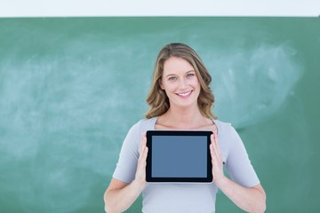 Smiling teacher holding tablet pc