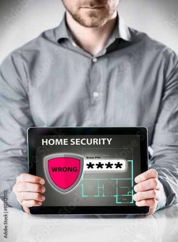 Leinwanddruck Bild Man Holding Tablet with Home Security Display
