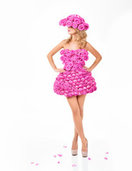 Beautiful woman in a dress and hat of flowers. Pink roses.