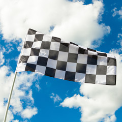 Checkered flag waving in the wind with clouds on background - ou