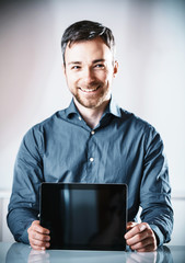 Young man holding up a blank tablet-pc