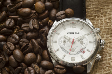 Silver watch with black leather belt and coffee beans