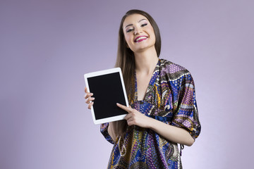 Smiling young woman pointing on blank digital tablet display