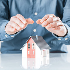 Man protecting his house with cupped hands