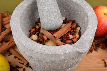 stone pestle grinding anise, nuts, pepper and cloves on wood