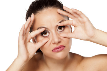 funny young woman holding her eyes open with her fingers