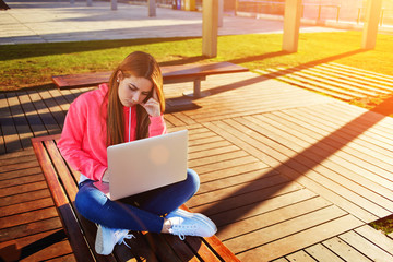Female student sitting with open laptop computer at campus