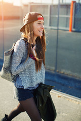 Young stylish teenager walking in the street at sunny evening