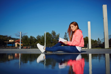 Female teenager reading book while sitting in the park