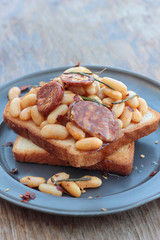 Toast with beans and chorizo on a tin plate.