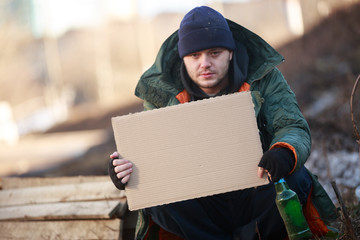 Homeless man holds blank cardboard for your text