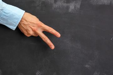 Man's hand gesturing on dark chalkboard with copy-space