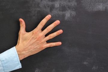 Man's hand gesturing on dark chalkboard with copy-space