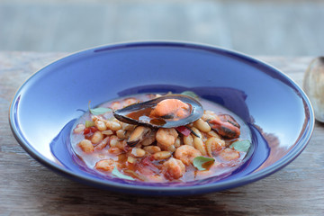 Beans and chorizo cooked with seafood on a blue plate.