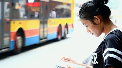 Asian woman reading a book in the streets of Hong Kong