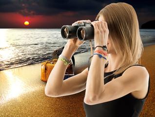 woman with binocular on the beach
